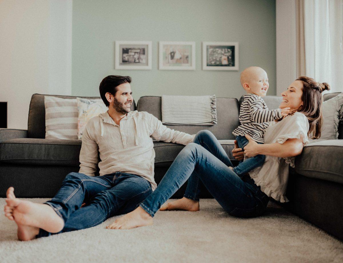 Familie sitzt vor dem Sofa auf dem Boden