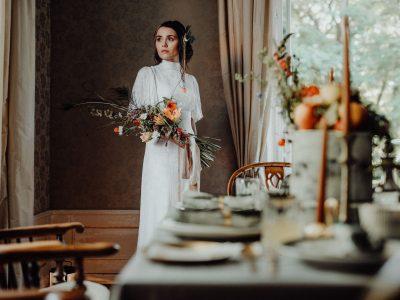 Braut steht hinter dem Tisch