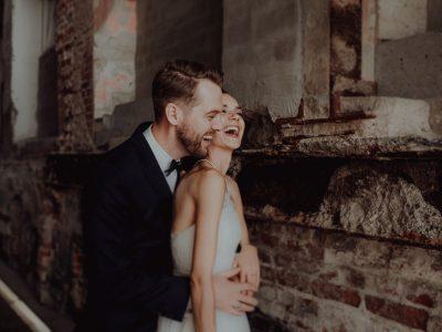 Bräutigam umarmt Braut von hinten